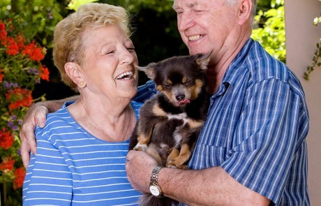 Two seniors happily holding their little puppy.